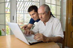 Senior man teaching laptop to his son